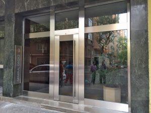 Puerta con dos fijos laterales y tres montantes, con perfil ancho en acero inoxidable.