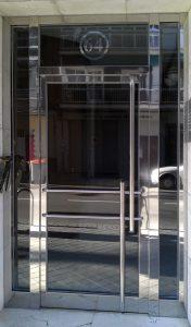 Puerta con dos fijos laterales y barra vertical en dos piezas. En acero inoxidable.