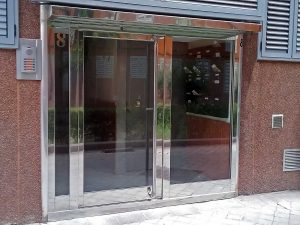 Puerta con dos fijos laterales desiguales y construida en acero inoxidable.
