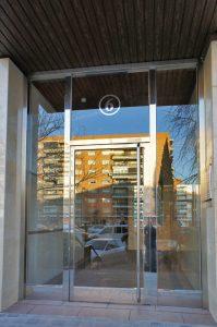 Puerta con dos fijos laterales, montante y tirador vertical, construida en acero inoxidable.